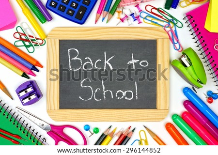 Back to School chalkboard on a white background with school supplies surrounding - stock photo