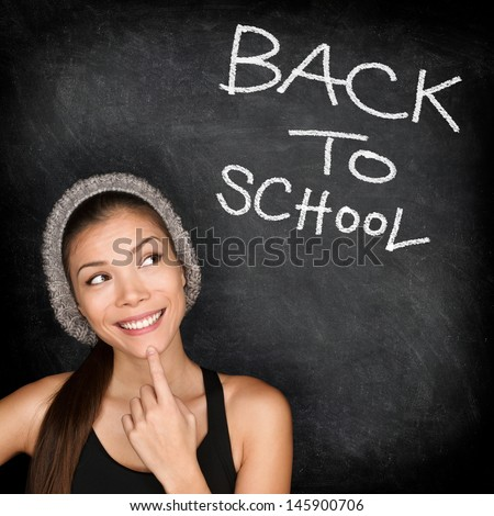 Back to school chalkboard - woman student thinking by blackboard. Female college university student girl thinking Back to School text. Modern trendy cool ethnic Asian Caucasian student in her 20s. - stock photo
