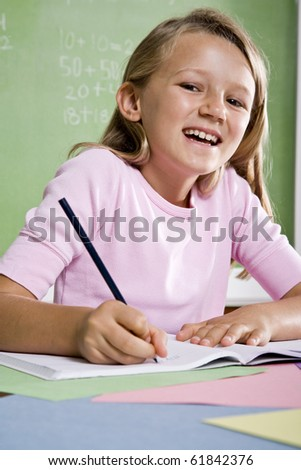 Back to school - close-up of 8 year old girl writing in notebook - stock photo