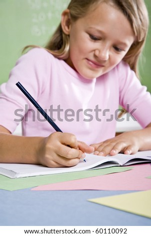 Back to school - close-up of 8 year old girl writing in notebook, focus on hand - stock photo
