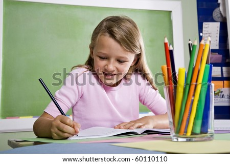 Back to school - close-up of 8 year old girl writing in notebook in classroom