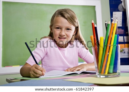 Back to school - close-up of 8 year old girl writing in notebook in classroom - stock photo