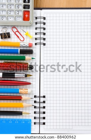 back to school concept and checked notebook on wood background - stock photo