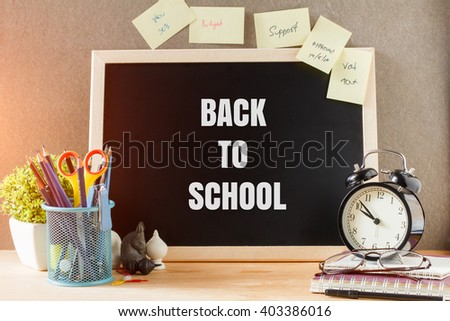 Back to school  concept. Blackboard with text inside BACK TO SCHOOL on table . office equipment - stock photo