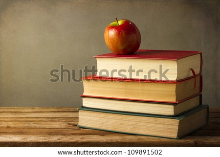 Back to school concept. Books and apple on grunge background
