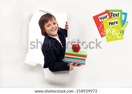 Back to school concept - boy with books looking through hole in billboard - stock photo