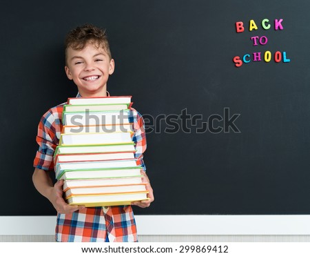 Back to school concept. Happy schoolboy with books at the black chalkboard in classroom. - stock photo