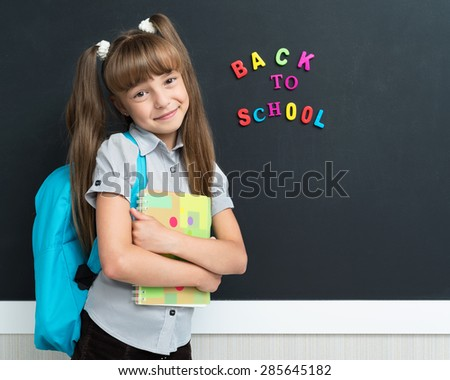 Back to school concept. Happy schoolgirl with backpack at the black chalkboard in classroom. - stock photo