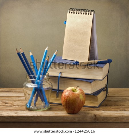 Back to school concept. Old books with pencils, apple and note book on wooden table.