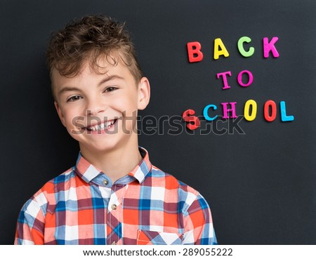 Back to school concept. Portrait of happy schoolboy at the black chalkboard. - stock photo