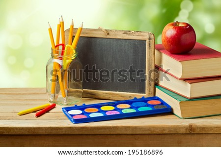 Back to school concept. School supplies on wooden table over green bokeh - stock photo