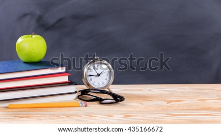 Back to school concept with green apple, pencils, clock, glasses and books in front of erased black chalkboard.