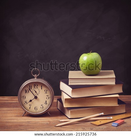 back to school concept with old schoolbooks, alarm clock and apple against a chalkboard background - stock photo