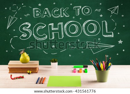 Back to school concept with writing on blackboard and desk, apple, books, items - stock photo
