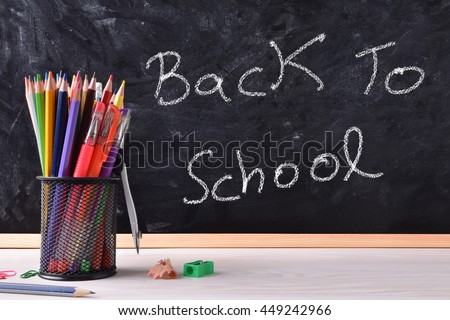 Back to school concept written with chalk on blackboard and container with school supplies on wood table. Front view - stock photo