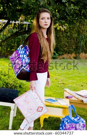 Back to school fashion girl showing bags, class book and accessories