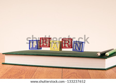 Back to school: floating wooden alphabet blocks on a book - stock photo