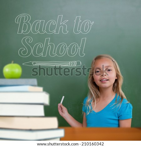 Back to school message against cute pupil holding chalk