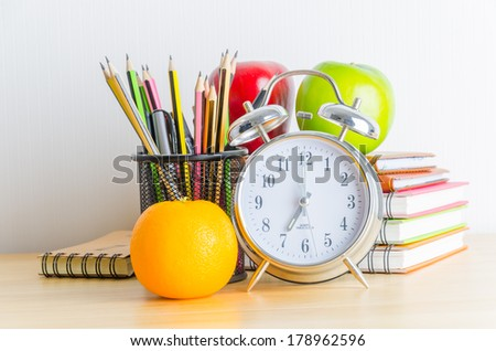 Back to school , note book , clock , pencil , apple on wood table - stock photo
