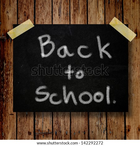 Back to school on message note with wooden background - stock photo