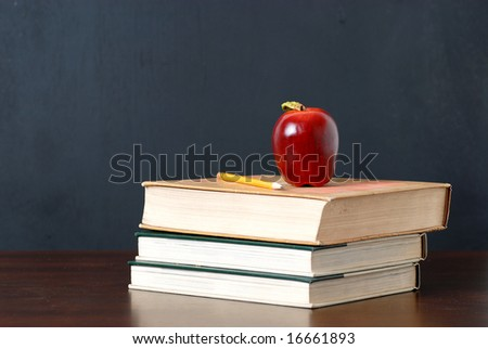 back to school, one apple on top the textbooks and pencil on the desk