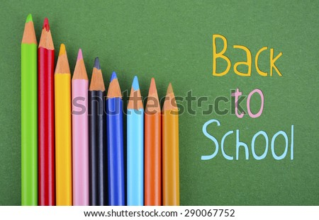 Back to School or Education Concept with colored drawing pencils overhead on green background and sample text. - stock photo