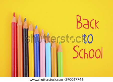 Back to School or Education Concept with colored drawing pencils overhead on yellow background and sample text. - stock photo