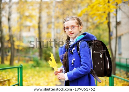 Back to school -  portrait of adorable brunette kid girl in blue coat and blue-white school uniform  and glasses with yellow maple  leaves in the autumn park