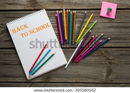 Back to School pupils art pencils and pad on wooden desk from above. - stock photo