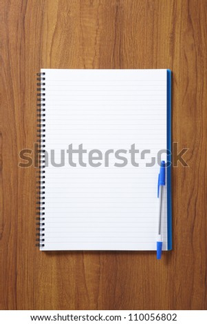 Back to School pupils note pad and pen on wooden school desk from above - stock photo