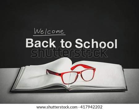 back to school, red glasses on the book with blackboard background