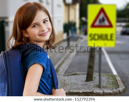Back to school - Road to the school -  portrait of lovely schoolgirl on a pedestrian crossing - stock photo