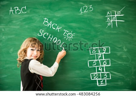 Back to school. Schoolchild in class. Happy kid against green blackboard. Education and creativity concept