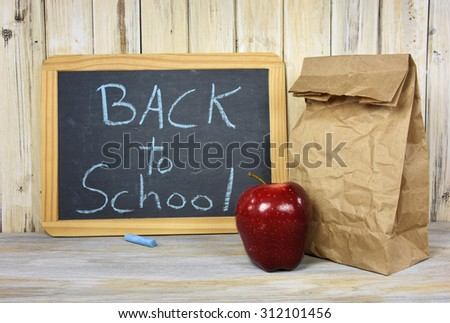 back to school sign on black chalkboard with paper sack lunch and red apple - stock photo