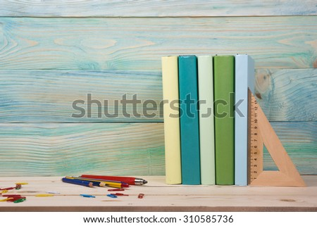 Back to school. Stack of colorful books on wooden deck table. Composition with vintage old hardback books, diary on blue wooden backdrop. Books stacking. Copy Space. Education background. - stock photo