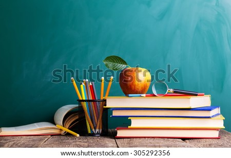 Back to school supplies. Books and blackboard on wooden background - stock photo