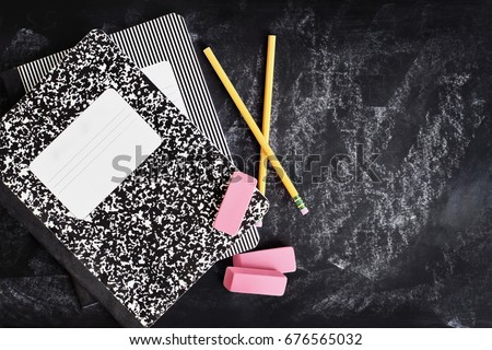 Back to school supplies. Books, erasers and pencils over a chalkboard or blackboard with room for copy space.