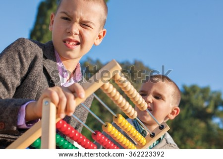 Back to school two confused little boys playing with wooden abacus in the park. One arround seven, the ather four. - stock photo