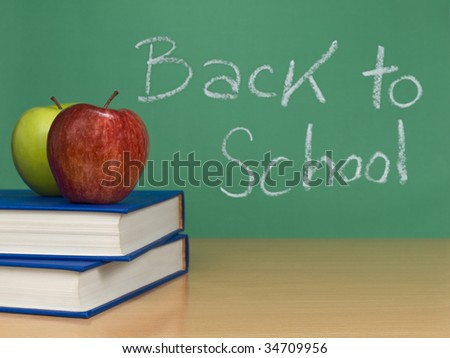 Back to school written on a chalkboard. Two apples over books on the foreground. - stock photo