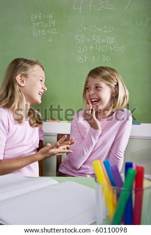 Back to school - 8 year old girls in classroom talking and smiling - stock photo