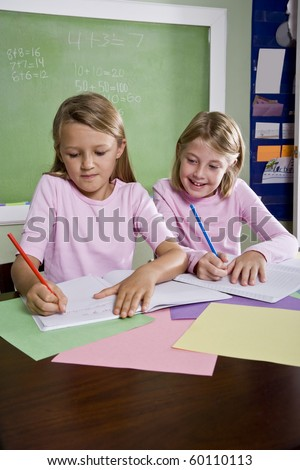 Back to school - 8 year old girls in classroom writing in notebook - stock photo