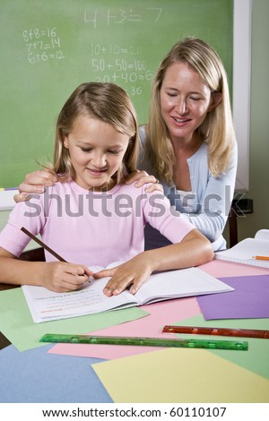 Back to school - 8 year old student and teacher writing in classroom - stock photo