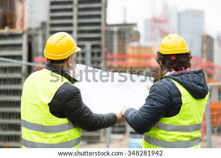 Back turned workers with yellow hardhat and safety jacket talking at construction site reviewing plans - stock photo