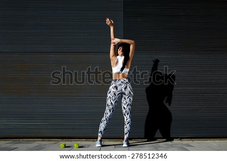 Back view athletic woman with perfect figure and buttocks stretching up her arms against wall with copy space for your text message, fit female in sportswear exercising on black background outdoors - stock photo