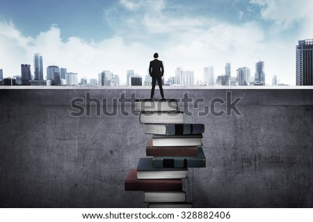 Back view business person looking the city, standing on the top of the book. Education for success concept - stock photo