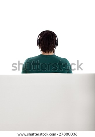Back view from a young man seated on the couch - stock photo
