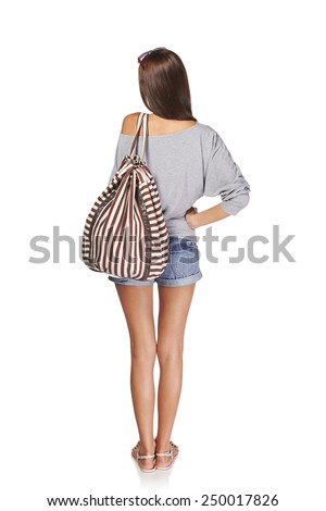Back view Full length of young slim tanned female in denim shorts with backpack, isolated on white background - stock photo