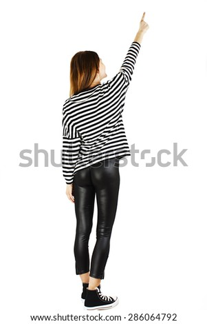 Back view Full length of young slim tanned female in leather pants and striped sweatshirt, pointing at blank copy space. Isolated on white background - stock photo