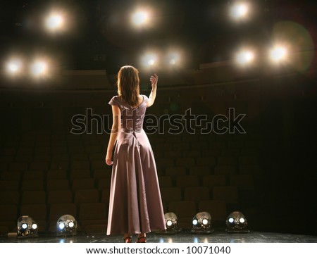 back view girl in long gown performing on stage - stock photo