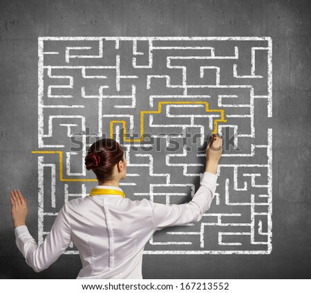 Back view image of young businesswoman trying to find way in labyrinth - stock photo